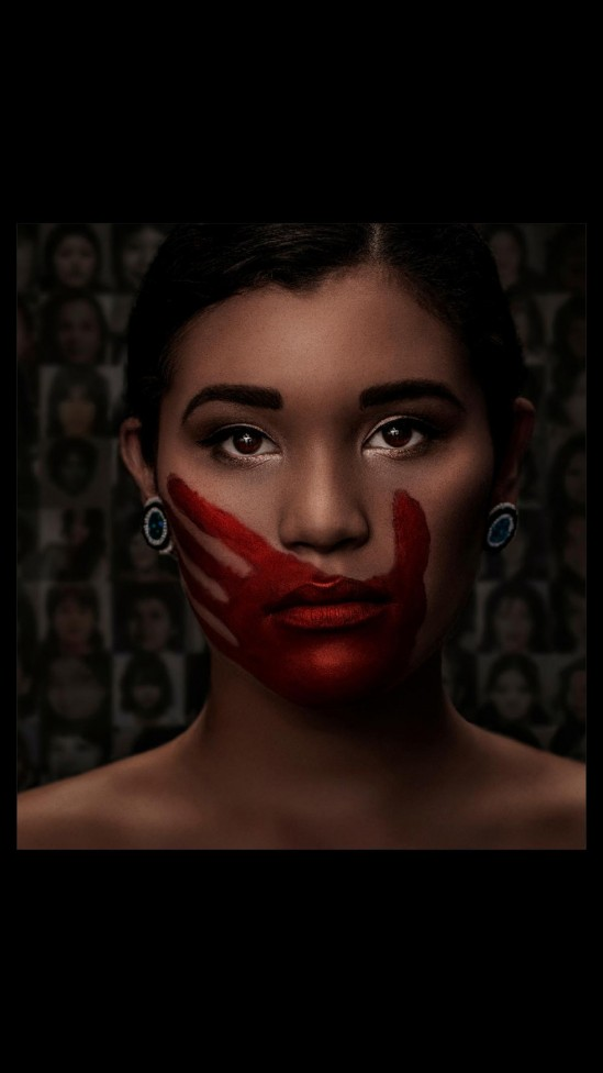 An image of an indigenous woman with a red hand over her mouth
