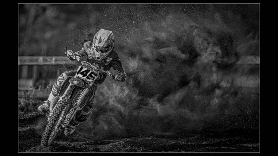 A black and white image of a motocross bike rider with a cloud of dust behind him.