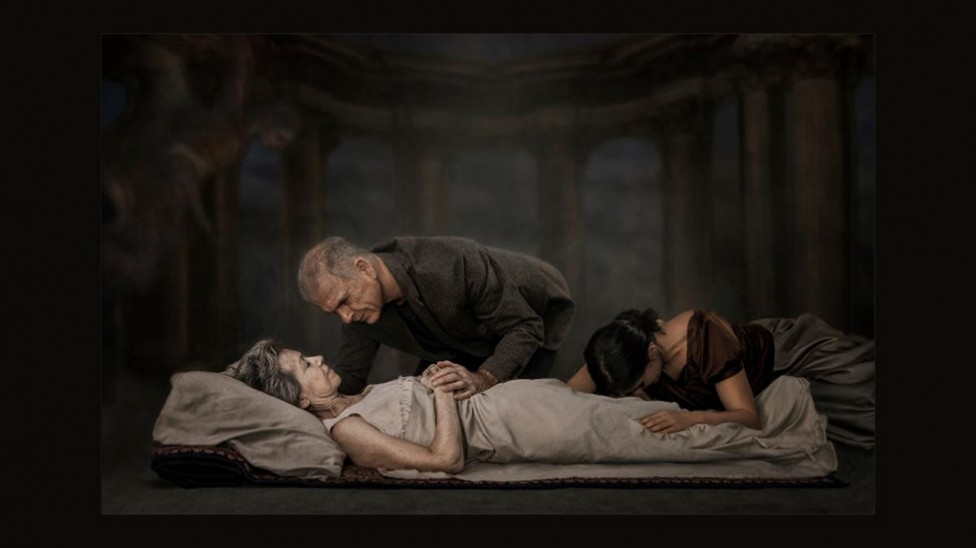 A man and a young woman grieve over a deceased or dying woman's body.