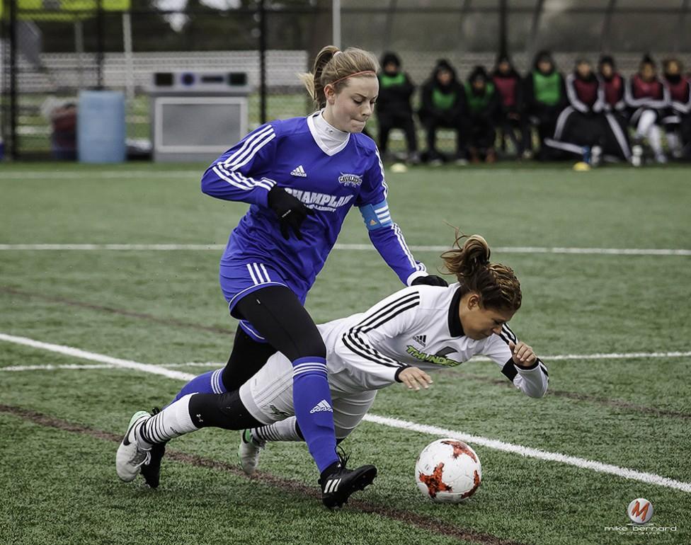 A well timed women's soccer photo by PE sports photographer, Mike Bernard