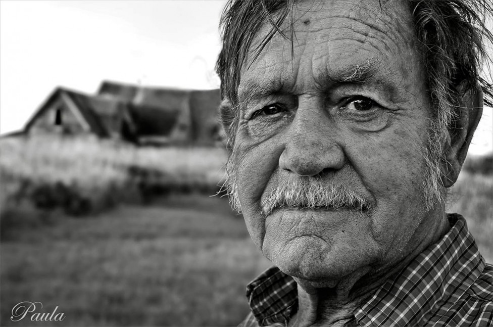 A gritty black and white portrait of a man with a weathered face and a dilapidated building in the background, by photographer Paula Lirette.