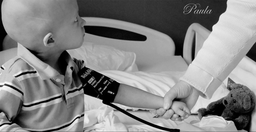 A photo of a bald child with a blood pressure cuff on his arm, holding hands with a person in a white coat. By photographer Paula Lirette.