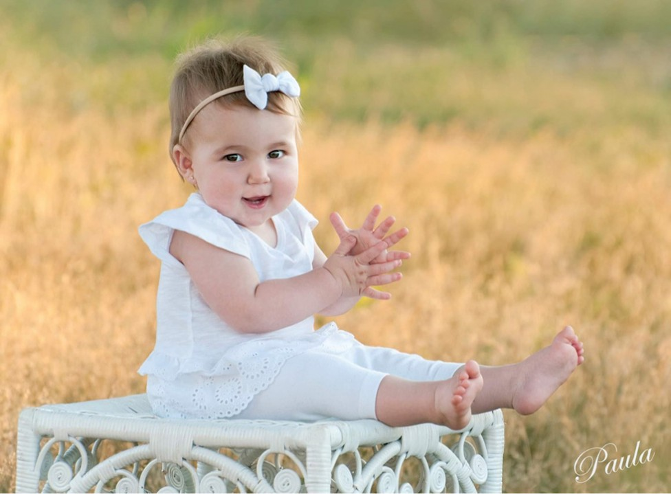 A warm summer scene of a toddler with a bow in her hair, dressed in white. By photographer Paula Lirette.