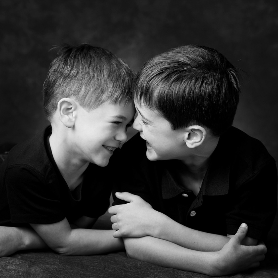 An adorable portrait of two little boys giggling together, by Louise Vessey