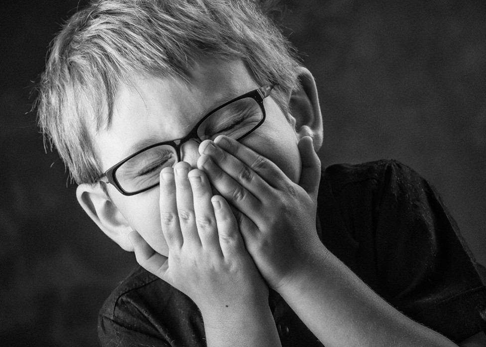 A little boy with glasses giggles shyly behind his hands in this portrait by Louise Vessey