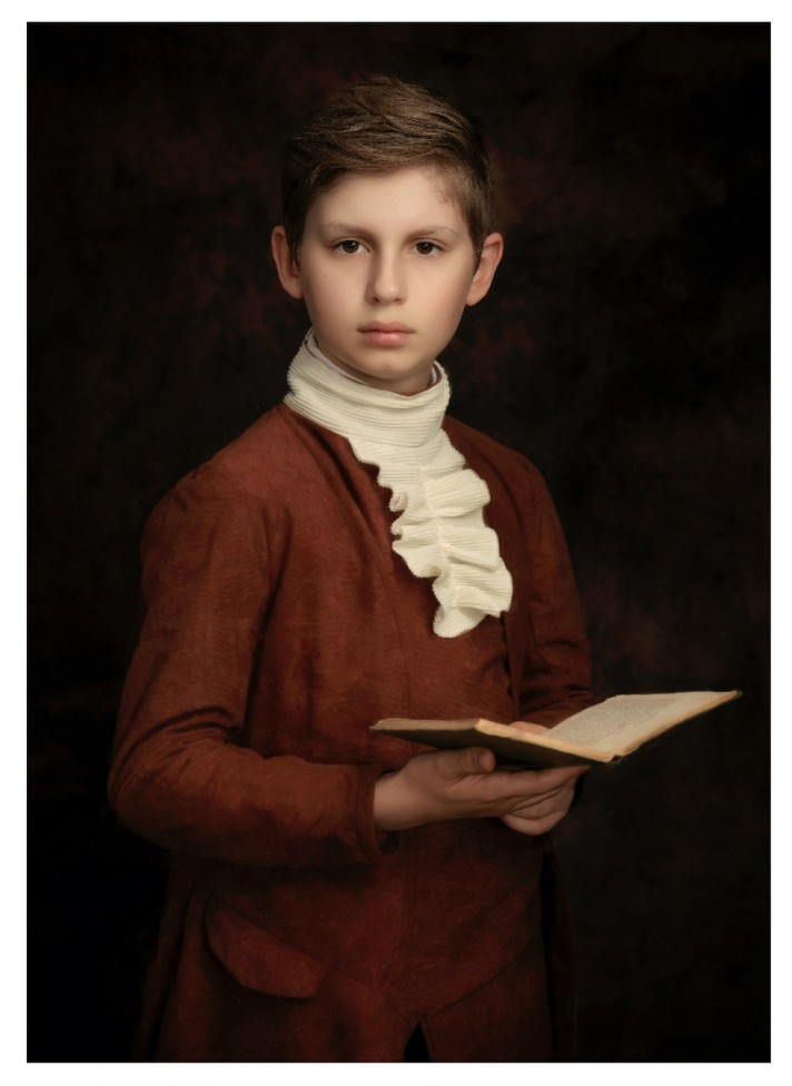 A portrait of a young man holding a book, by Jamie Bard